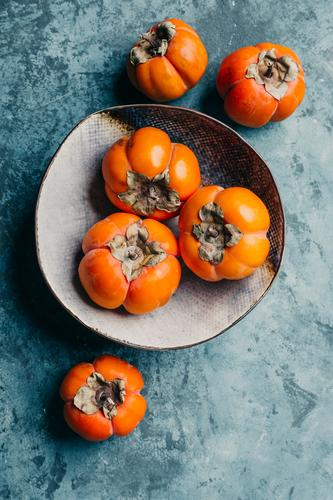 Delicious persimmon in a plate on a blue background sweet fresh juicy healthy orange food organic diet ripe vegetarian fruit nutrition delicious natural tasty