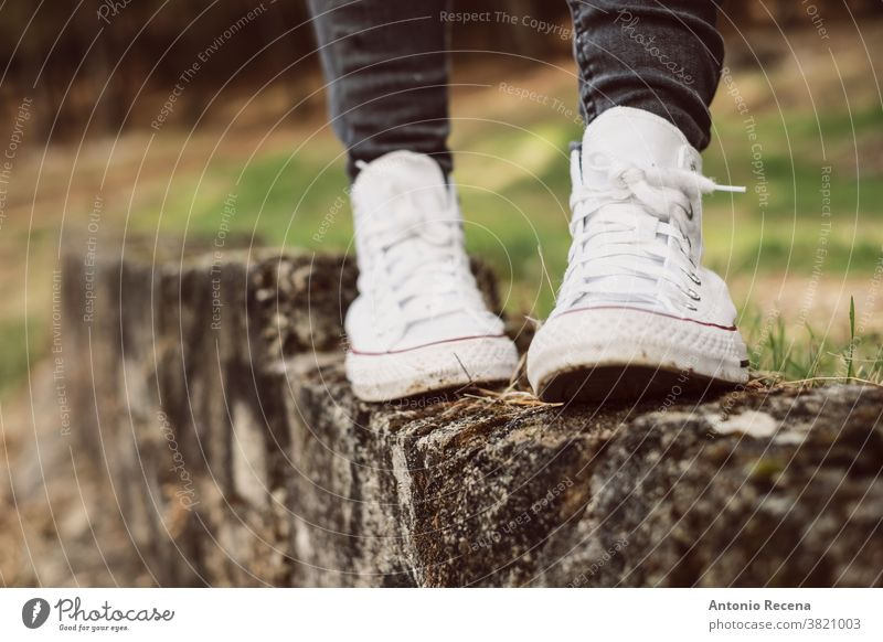 Feet in white sneakers balancing on a wall outdoors feet foot walking snickers shoe shoes balance legs woman forest partition anonymous closed frame fashion