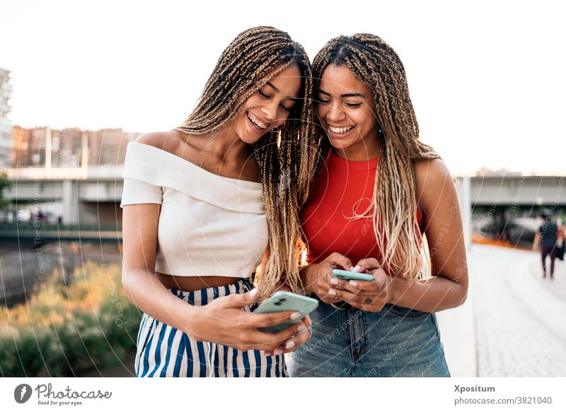 Happy Sisters Using Phone using phone typing smiling front view sisters african american braids street attractive young style expression beautiful pretty ethnic