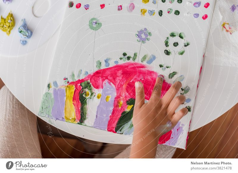 Hands of a little girl panting in a Canvas with her fingers. colours childhood smile art funny draw creativity learning beautiful paint happy education white