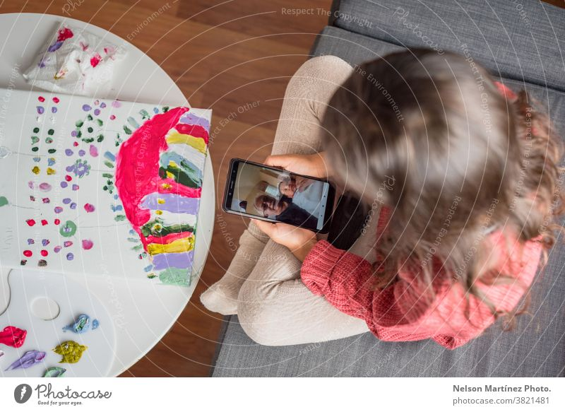 Little Kid holding a smartphone while she is chatting with her grandfather in the cell phone. greeting funny skype care call talking happy hallo online family