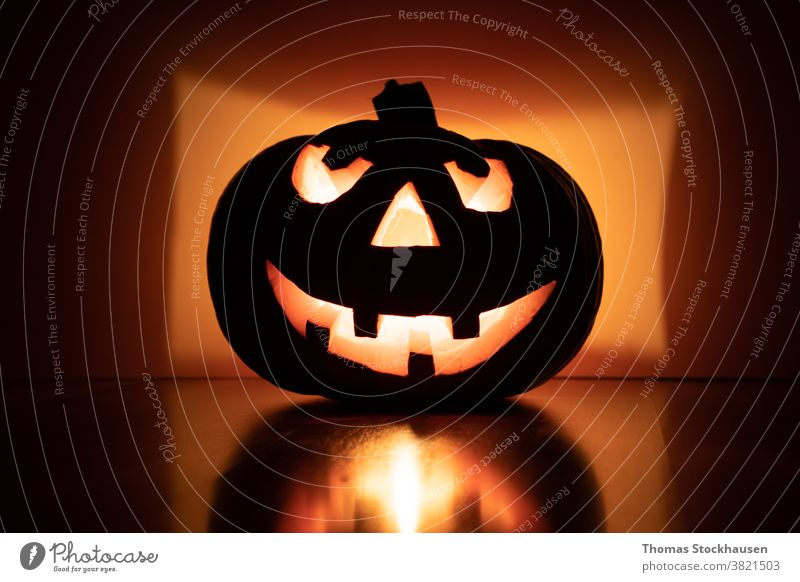 Halloween pumpkin with smiling face on reflective background, four teeth. Light that illuminates the pumpkin from inside Autumn Black cauterizing shoulder stand