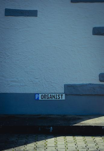 """Parking reserved for the """" ORGANIST """", A parking sign attached to a wall. Reserved Parking lot Signs and labeling Street Asphalt Signage Deserted Characters"""
