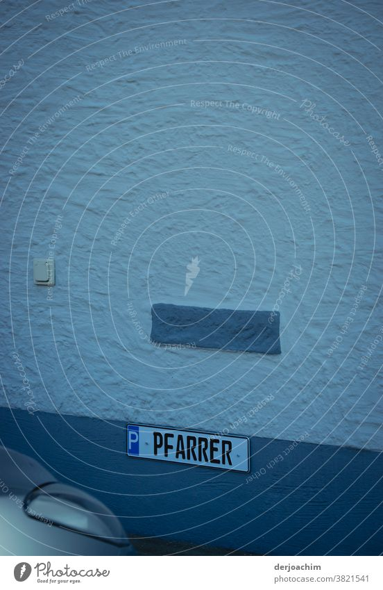 Parking for the PFARRER. Unfortunately it is occupied by an unknown car. The sign is attached to a white wall with blue gradations. In the lower edge of the picture on the left, a headlight is to be recognized.