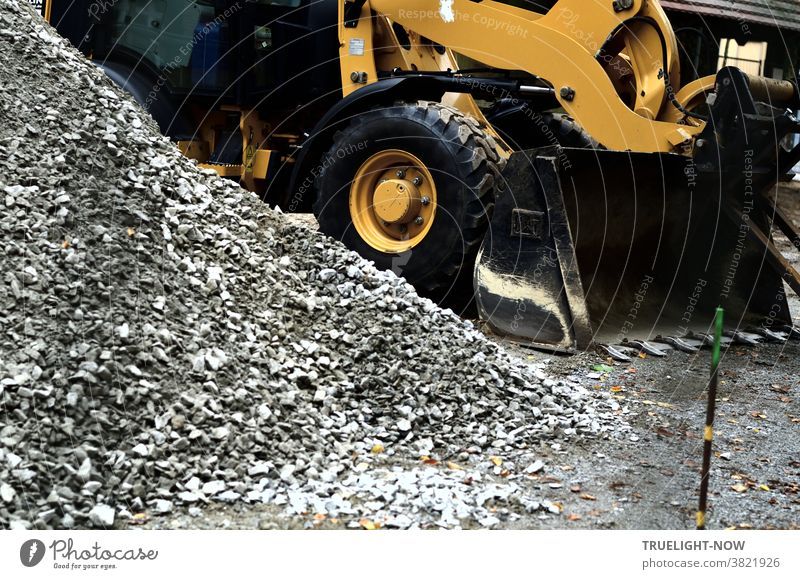 Road construction and landscaping with a heavy yellow wheel loader, thick black tyres and loading shovel next to a grey heap of coarse-grained sand or gravel and a thin iron bar stuck crooked in the ground