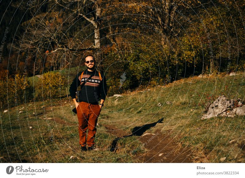 A young man stands in an autumnal landscape and smiles Man Nature Landscape Autumn Trip Hiking sunshine golden autumn Beautiful weather Forest Meadow Good mood