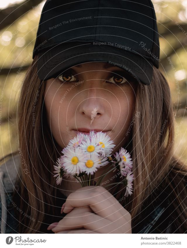 Closeup of an attractive brunette holding a bouqet of small white hand picked flowers on her lips, bright colorful amber eyes looking straight into the camera. Wearing a black cap in nature