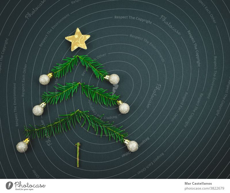 Christmas tree made with pine branches on a black background. decoration christmas end of the year star balls space copy christmas tree decorations concept