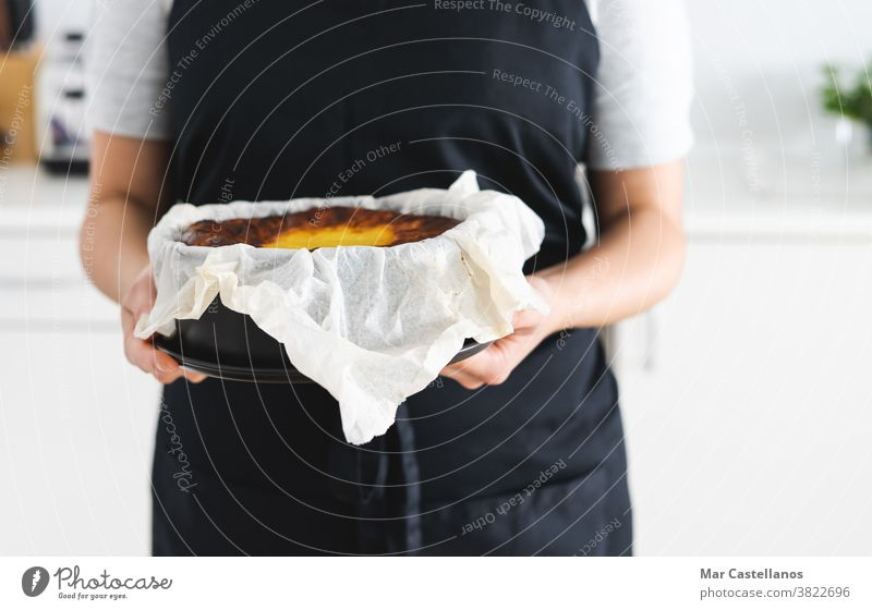 Woman in black apron showing a cheesecake. Cheesecake Copy space marble chef cook woman hands dessert sweet delicious paper kitchen pastries baked burned creamy