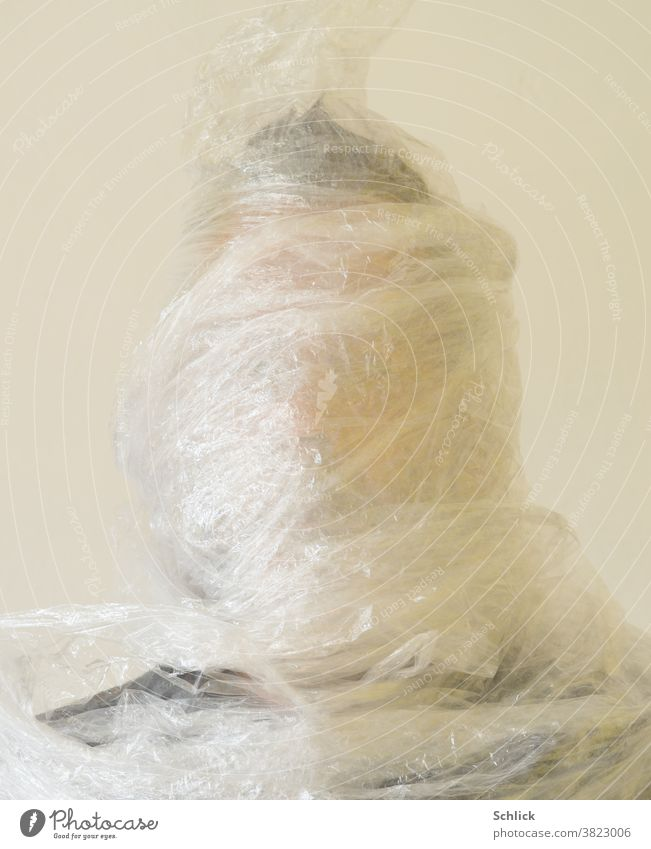 Plastic mania Head of a man wrapped in stretch foil Packing film plastic portrait Wrapped around Man stretch film Environmental protection plastic waste Trash