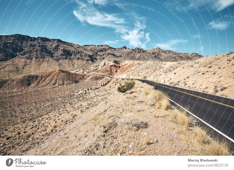 Scenic desert road in Valley of Fire State Park, Nevada, USA. highway trip landscape nature sunny retro vintage drive America travel valley mountain canyon