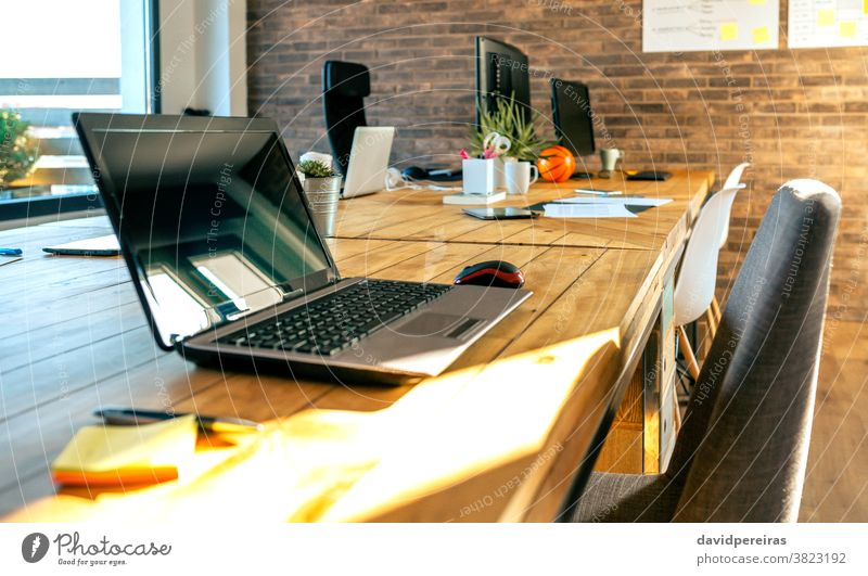 Interior of industrial style coworking office empty laptop workplace desk table informal brick wall computer window room creative interior modern business