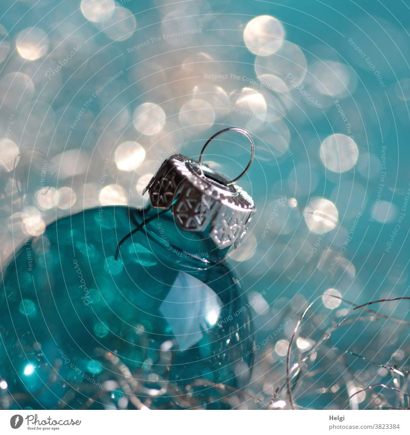 Christmas glitter - turquoise blue glass Christmas ball with silver hanger in front of turquoise white background with bokeh christmas ball Glass ball