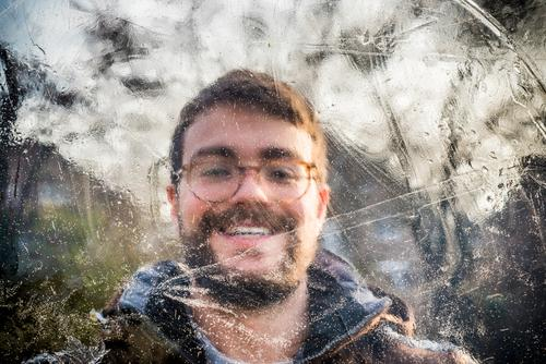 Portrait of a smiling young man behind ice Young man smilingly Facial hair Eyeglasses Brunette person masculine Winter Ice Frozen Cold Brown Green Day daylight