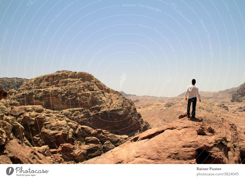 Young man on top of a peak looking over a valley in the rugged landscape of Petra, Jordan adventure copy space desert explore the world explorer future concept