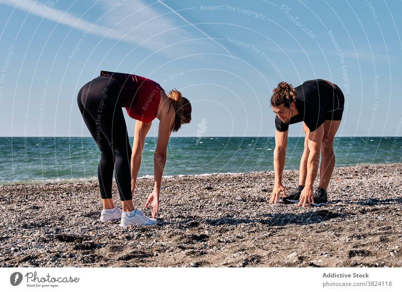 Sportswoman and trainer warming up at seaside forward bend warm up training personal instructor sportswoman sportsman seashore stretch stand athlete flexible