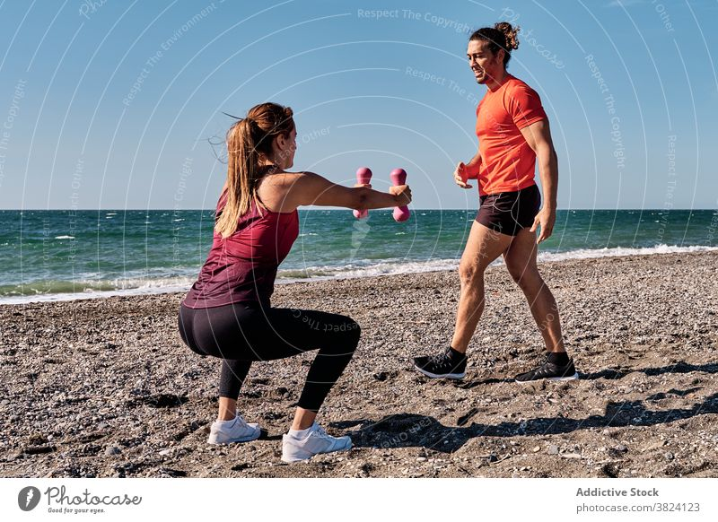 Fit woman doing exercises with help of trainer squat training sportswoman instructor personal workout dumbbell fit beach summer sportswear sea wellness vitality