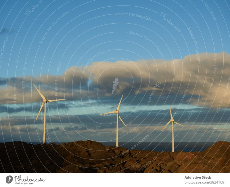 Amazing view of windmills in countryside at sunset alternative energy resource sustainable eco friendly development sea hill modern scenic ecology renewal
