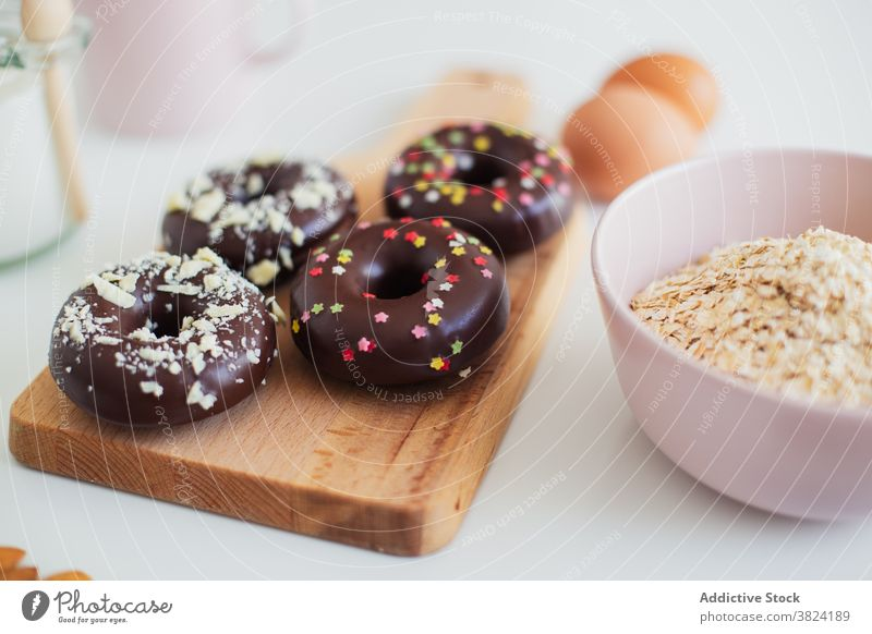 Donuts and ingredients for recipe on table donut doughnut pastry dessert sweet prepare food cook chocolate egg sprinkle almond delicious sugar culinary cuisine