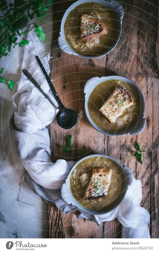Bowl of french onion soup on wooden surface cream soup vegetable bowl bread cuisine food foodcollection herbage veggies cooked lunch cheese crouton dinner