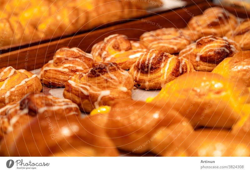Bakery in brown wooden tray in bakery shop. Fresh bake pastry product. Sweet bread display on counter. Carbohydrates food. Snack for breakfast or lunch. Bakery retail shop. Homemade bakery business.