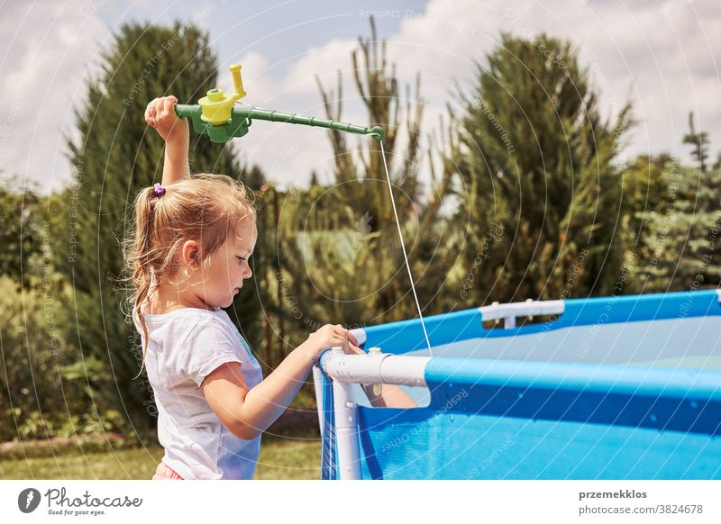 Children playing with fishing rod toy in a pool in a home garden authentic backyard childhood children family fun happiness happy joy kid laughing lifestyle