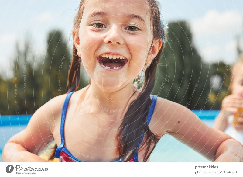 Portrait of happy smiling girl standing in a pool having fun on a summer sunny day authentic backyard childhood children family garden happiness joy kid