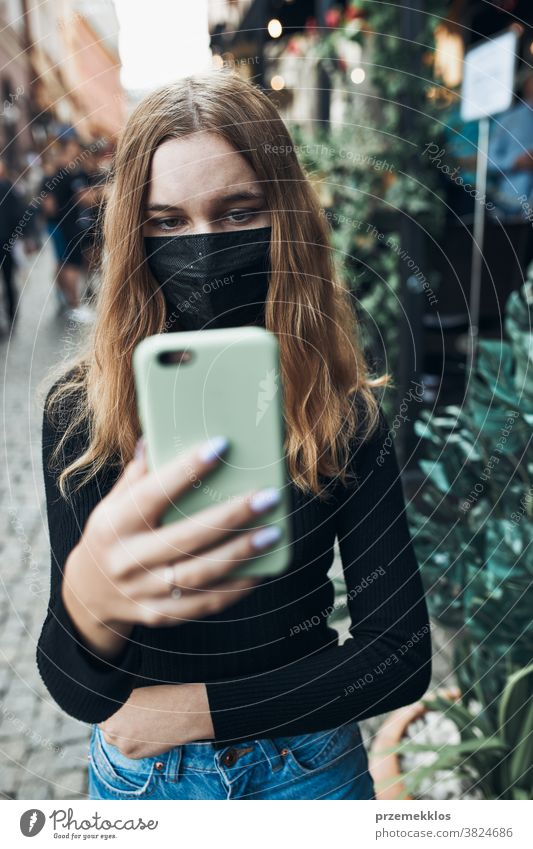 Young woman having video call talking while walking downtown wearing the face mask to avoid virus infection care caucasian chat contagious corona coronavirus