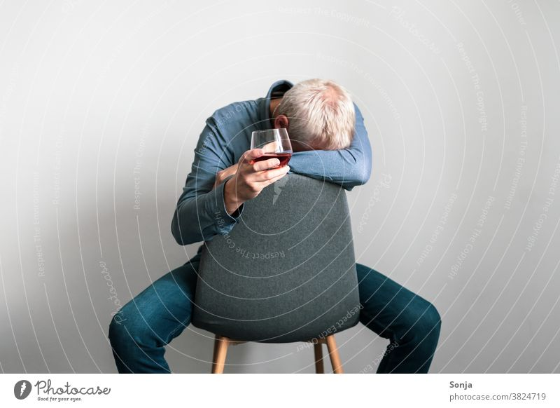 Depressed man sitting on an armchair with his head on one arm and a glass of cognac in his hand Man depression Distress Loneliness sad unhappy Lonely Armchair