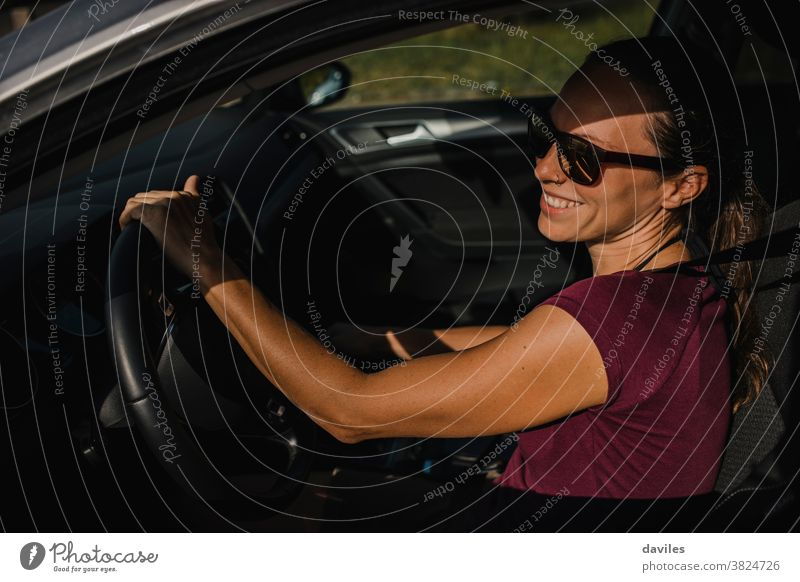 Woman in her car holding the steering wheel and smiling. drive carefree laugh happy smile joy cheerful young adult connection road trip real people vacations