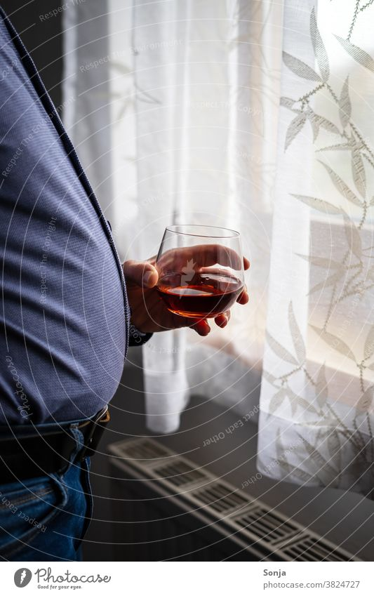Overweight man with a glass of cognac standing at a window Man Cognac drinking glass Hand stop Window Observe Loneliness at home stay at home Fat coronavirus