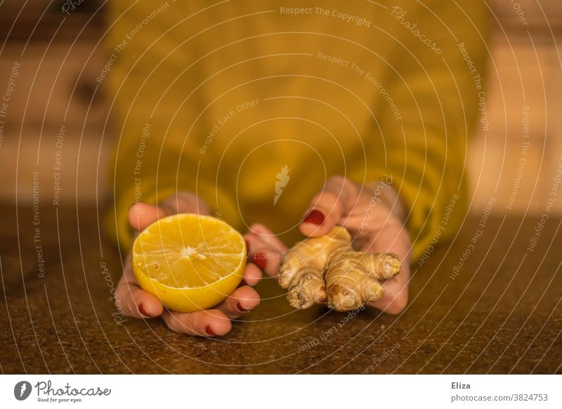 Strengthen the immune system during the cold season: Woman holds half a lemon and a piece of ginger. Ginger Lemon salubriously Common cold cold spell