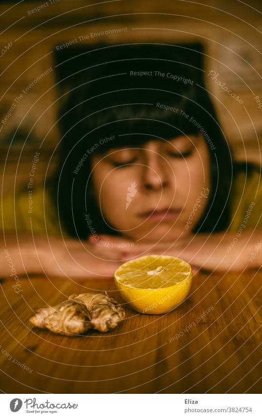 A woman is tired, limp and cold and lies with her head on the table behind ginger and lemon. Common cold listless Ginger Sick Lemon immune system