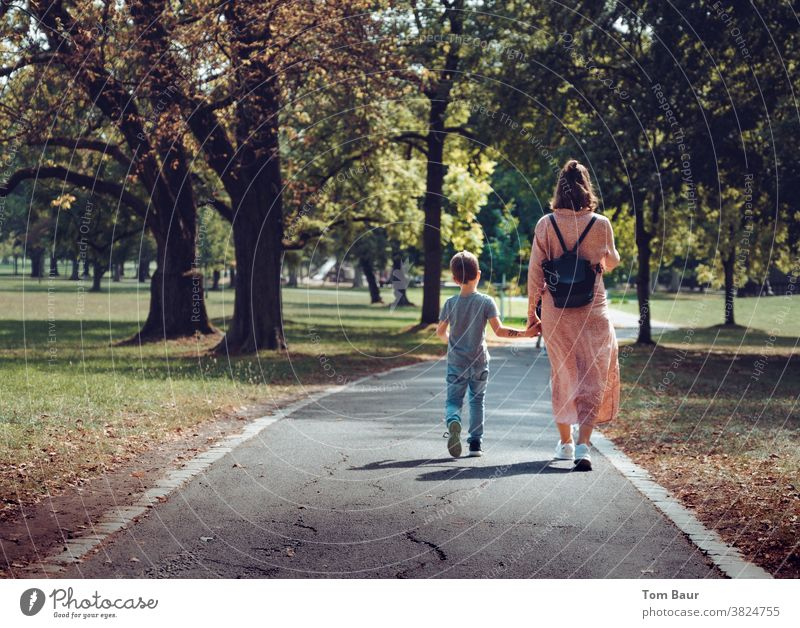 Hand in hand mother with child walking through an autumnal park Town To go for a walk Promenade stroll take a walk Hold hands Child Mother with son Young woman