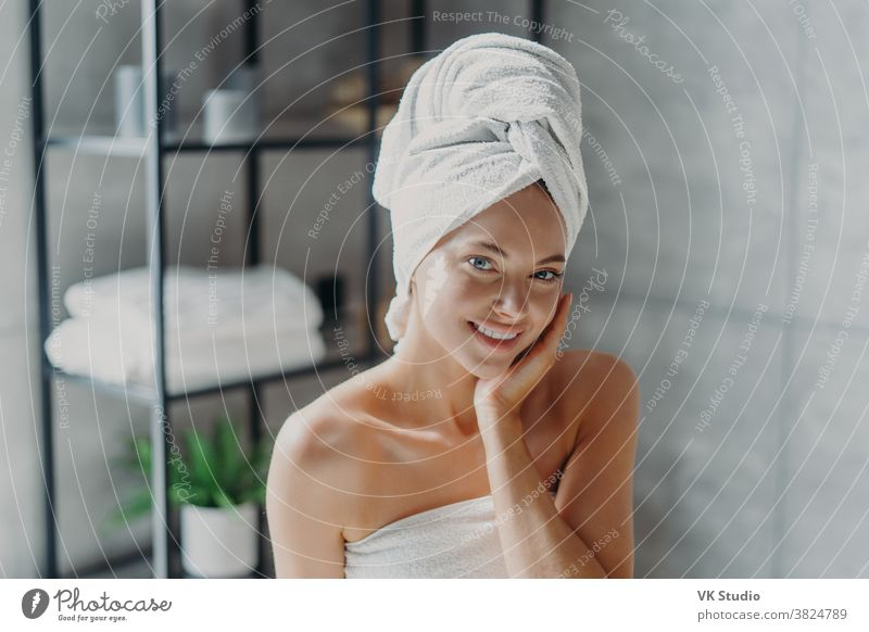 Beautiful European woman with makeup touches skin, has minimal makeup, has healthy glowing skin, wrapped in bath towel, enjoys rest at home. Spa woman poses in bathroom. Beauty, wellness concept