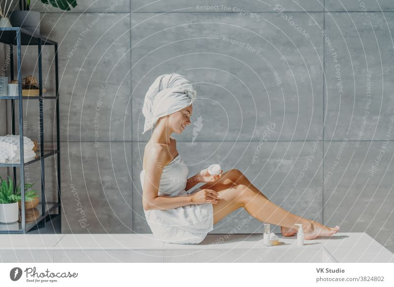 Horizontal shot of relaxed young European woman applies moisturizing body cream on legs, wrapped in bath towel, has tender smile, healthy refreshed skin after taking bath, poses in cozy bathroom.