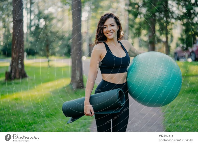 Sporty European woman in cropped top and leggings, carries rolled up karemat and fitness ball, going to have aerobics exercises, poses outdoor against green nature background, has pilattes class