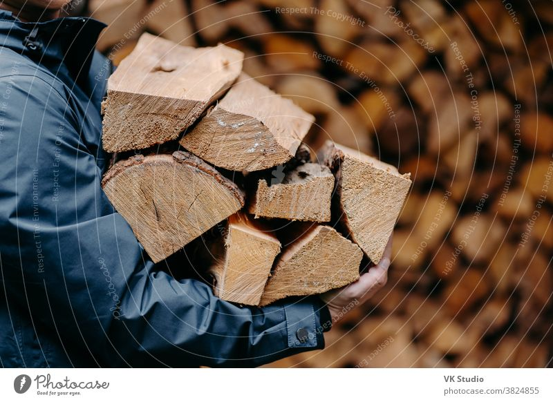 Unrecognizable man carries heap of wood for making fire dressed in jacket. Faceless male carries firewood into house wooden outdoors log fuel chop woodcutter