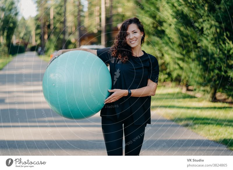 Outdoor shot of brunette woman poses with big fitball, dressed in sportclothes, has training in open air, walks on road, poses near forest. Fitness trainer going to show masterclass for pregnant women