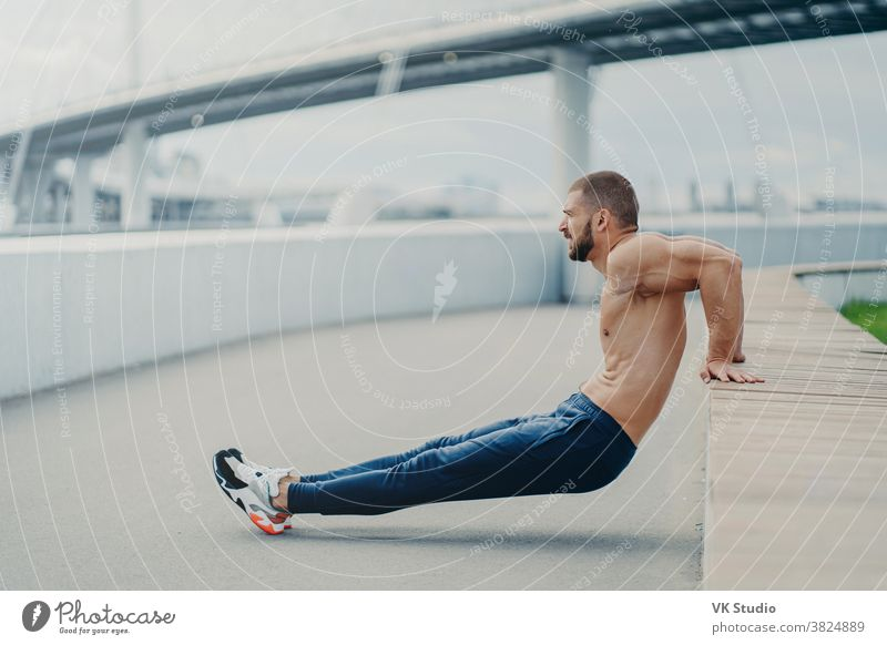 Sideways shot of muscular man does reverse push up exercise, trains arms, keeps perfect body and good physical shape, has active workout outdoor, wears sport trousers and sneakers, poses on bridge