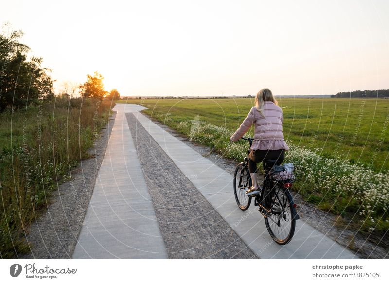 Woman riding a bike in the sunset Cycling Bicycle Field Sunset Driving Cycling tour Lanes & trails Movement Mobility Trip Leisure and hobbies Blonde off
