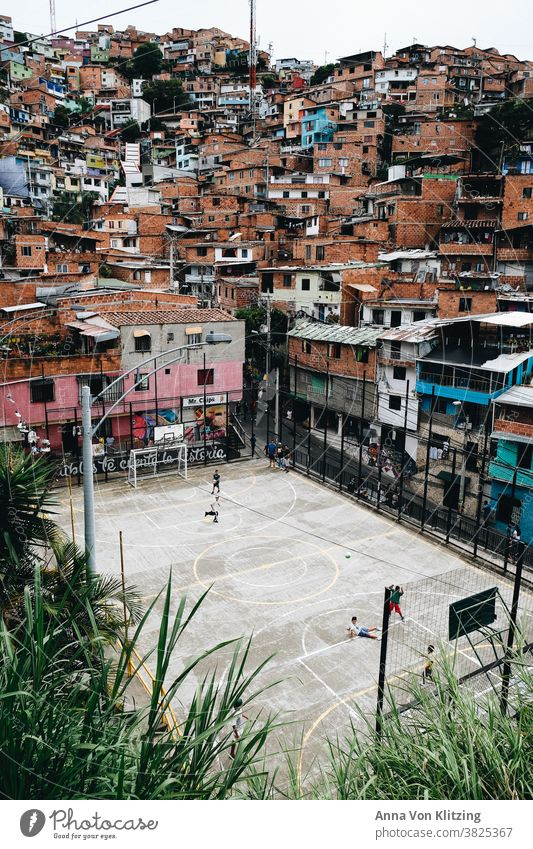 Football pitch in Medellin Foot ball medelline colorful houses Playing children variegated Colombia Town urban densely populated colourful playing children