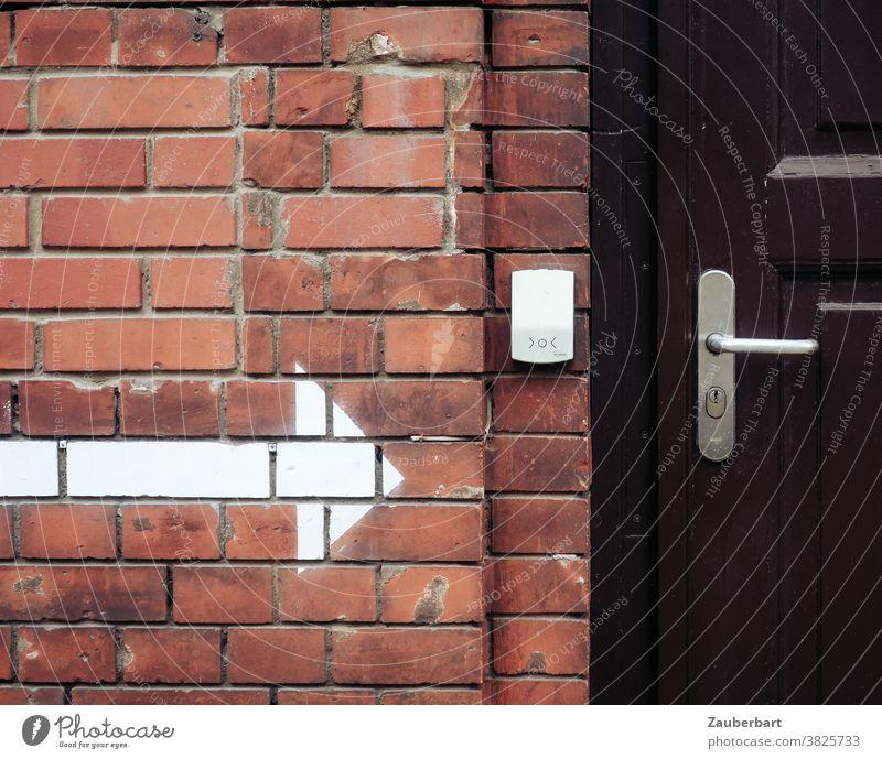 brick wall, white arrow, bell and wooden door Arrow Indicate Wall (building) clinker Brick red door handle Entrance Clue Wooden door Brown locked Road marking