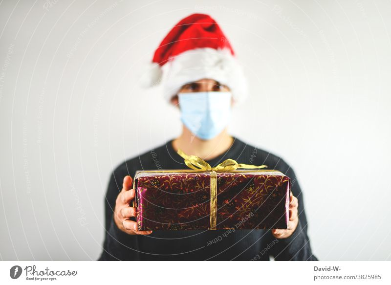 merry christmas - man holds gift in his hands under corona conditions Christmas Gift Respirator mask Mask Santa Claus hat Giving of gifts pandemic Protection