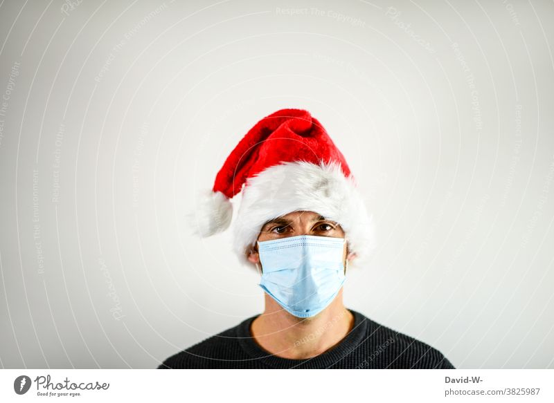 Corona and Christmas - Man with breathing mask and Santa cap Mask corona Santa Claus hat advent season pandemic coronavirus Risk of infection Protection Healthy