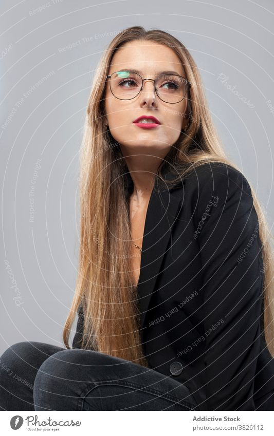 Stylish woman in trendy outfit in studio smart casual model style stool wooden charming female beauty content blond long hair gorgeous vogue sit modern calm