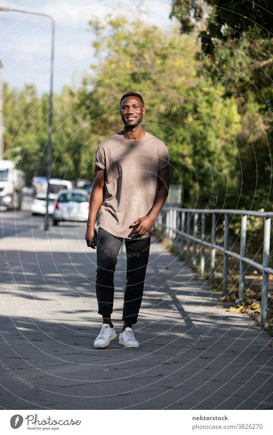 Young Black Man Walking on City Sidewalk man black smile african ethnicity sidewalk street genuine sincerity real life real people full length looking at camera
