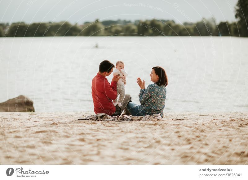 happy family resting by the lake. family with a small child nature parent mother daughter summer love together holiday happiness fun girl father smiling cute
