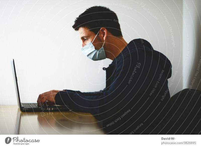 Quarantine and home office - man works with breathing mask on laptop corona Respirator mask Mask by oneself Lonely Corona virus pandemic