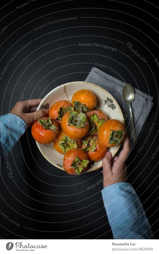 Plat of persimmon and hands autumn biologic black background copy space dark delicious food fruits good healthy holding indoor many nutrition orange plat spoon